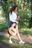 young woman walking in the forest and playing guitar, summer nature, bright sunlight, shadows and green leaves, romantic feelings - 221008940
