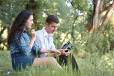 young couple sitting on the grass in the forest and looking on sunset, listen to radio, summer nature, bright sunlight, shadows and green leaves, romantic feelings - 221008961