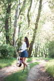 young woman walking in the forest and playing guitar, summer nature, bright sunlight, shadows and green leaves, romantic feelings - 221008979
