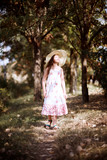 a girl walks along a forest path, dressed in a long dress and wide hat, bright sun and shadows, a beautiful summer day - 221009140
