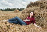 young girl having fun in the field, lying on a haystack - 221009162