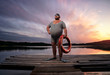Leinwanddruck Bild - Fuunny overweight, retro swimmer by the lake, at the sunset with copy space