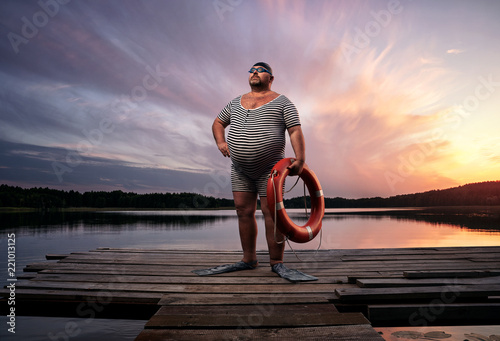 Leinwanddruck Bild Fuunny overweight, retro swimmer by the lake, at the sunset with copy space