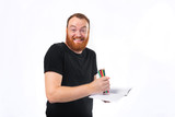 Adult bearded man grinning with madness at camera while drawing with heap of colored pencils on paper - 221013761