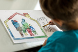 Child colouring in a sketch of a family using a paintbrush