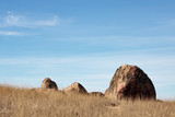 One large boulder and three smaller big rocks set against blue sky with white wispy clouds, dry grass in foreground