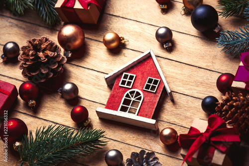 little wooden house and Christmas decoration on wooden table. Above view in old color style - 221036332