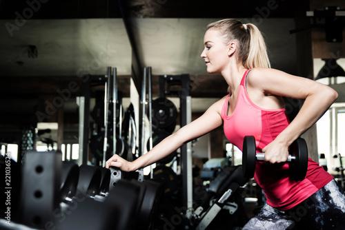 Młoda kobieta w siłowni, ćwiczenia z hantlami