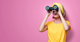 Young redhead girl in yellow t-shirt and blue jeans holding binoculars on pink background - 221039917