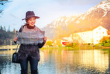 Young female tourist looking at a map in a beautiful town Interlaken, Switzerland, Europe. - 221050503