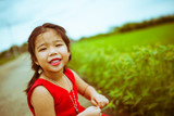 smiling kid girl in red dressing with green grass background process in vintage tone - 221067999