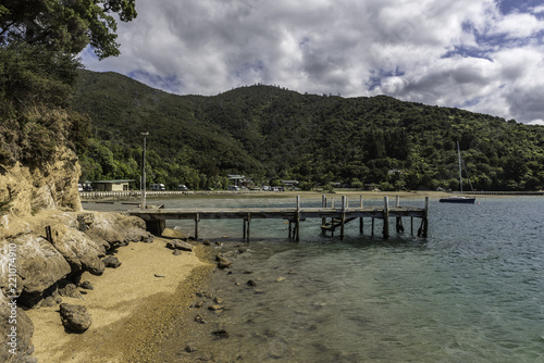 The old wooden pier at Momorangi Bay on a sunny day in the Marlborough Sounds, Nelson, New Zealand.