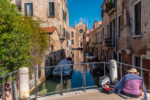 Fototapeta VENICE, ITALY, CANAL - A view from a bridge into a narrow side canal, to the Roman Catholic church Madonna dell'Orto. A gothic building.