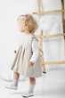 Portrait of a little girl near the ladder in the midst of clouds on a white background