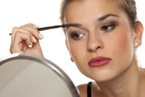 Young woman contouring her eyebrows with dry brush on white background - 221080159