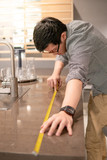 Young Asian man using tape measure for measuring granite countertops on modern kitchen counter in showroom. Shopping furniture for home improvement. Interior design concept - 221081929