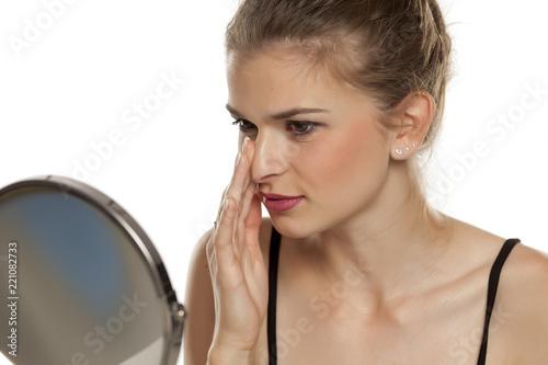 Leinwandbild Motiv Profile of young woman touching her nose on white background