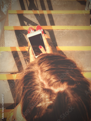 Poster Woman using cellphone / smartphone while sitting on the stairs in urban surroundings.