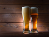 Two glasses of golden beer on wooden background - 221089915