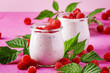 Raspberry smoothie in glass jar with fresh berry and greek yogurt on pink stone background, selective focus