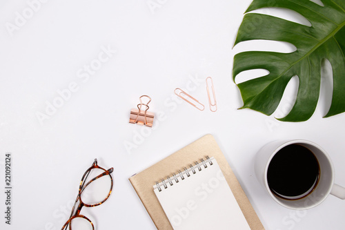 Leinwanddruck Bild Mock up workspace with tropical palm leaf,  glasses, notebook and coffee cup on white background. Flat lay, top view. stylish female concept.
