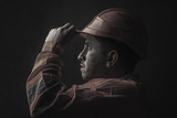 dramatic portrait of tired rail worker who hold his safety helmet