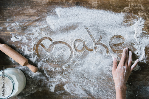 cropped shot of woman writing word BAKE with finger on rustic wooden table covered with flour - 221096387