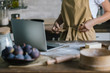 cropped shot of woman with laptop and pie ingredients on rustic wooden table tying up apron
