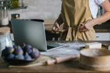 cropped shot of woman with laptop and pie ingredients on rustic wooden table tying up apron - 221096706