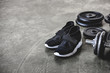 Leinwanddruck Bild - close-up shot of weight plates and sneakers on concrete floor