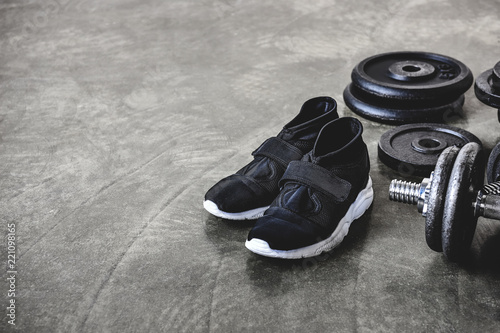 Leinwanddruck Bild close-up shot of weight plates and sneakers on concrete floor