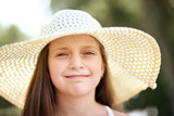 portrait of a little girl wearing a big hat, beautiful sunny day, bright sun and shadows, face closeup - 221098945