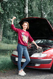 a young girl stands at a broken car and holds a bad spare part, an electric generator, shows a success gesture, repair completed - 221099188