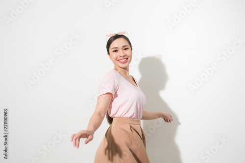Fototapeta Portrait of a happy young woman dancing on white background
