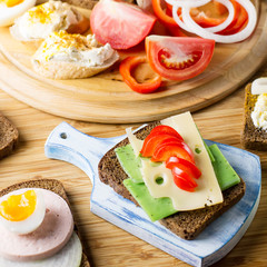 Breakfast table with cheese sandwiches, sausage, vegetables, hard boiled eggs and fruits