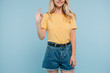 cropped image of girl in shirt and shorts showing okay gesture isolated on blue