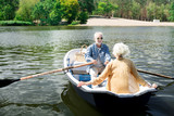 Bearded husband. Bearded elderly husband sitting in boat with beautiful wife while having very romantic date - 221116196