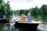 Summer day. Aged beaming wife and husband feeling relaxed while sitting in little boat on warm summer day - 221117136