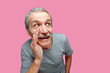 Funny senior man telling the secret against pink background