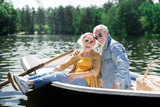 Smiling pensioners. Smiling cheerful pensioners feeling very happy while sitting in little boat while having romantic date - 221117376