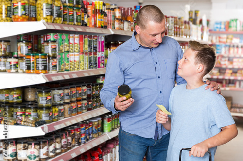 portrait of father and boy choosing food with shopping list buy