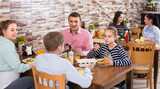 family with teenage children enjoying meal in cafe - 221128928