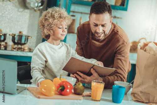 Young cook. Curious cute child reading a recipe while spending time with father