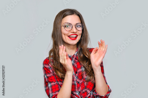 Bright young woman in round glasses and a red checkered shirt is relaxed and applauds