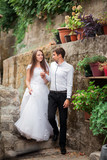 The bride and groom go hand in hand. Couple in love in white dresses on the background of an old stone wall, flowers and flowerpots. Wedding day in Kotor, Montenegro - 221133758