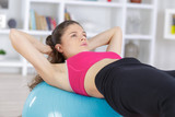 young woman doing abs exercise on the big ball - 221134354
