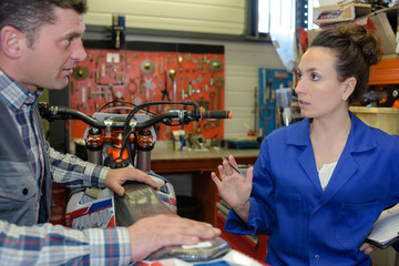 male and female mechanics in discussion over seat of motorcycle