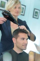 Hairdresser drying man's hair © auremar
