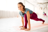 fitness, sport and healthy lifestyle concept - smiling woman making high lunge exercise at yoga studio - 221135577