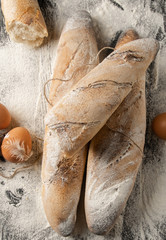 Still life of baguette from the stove on the table with flour